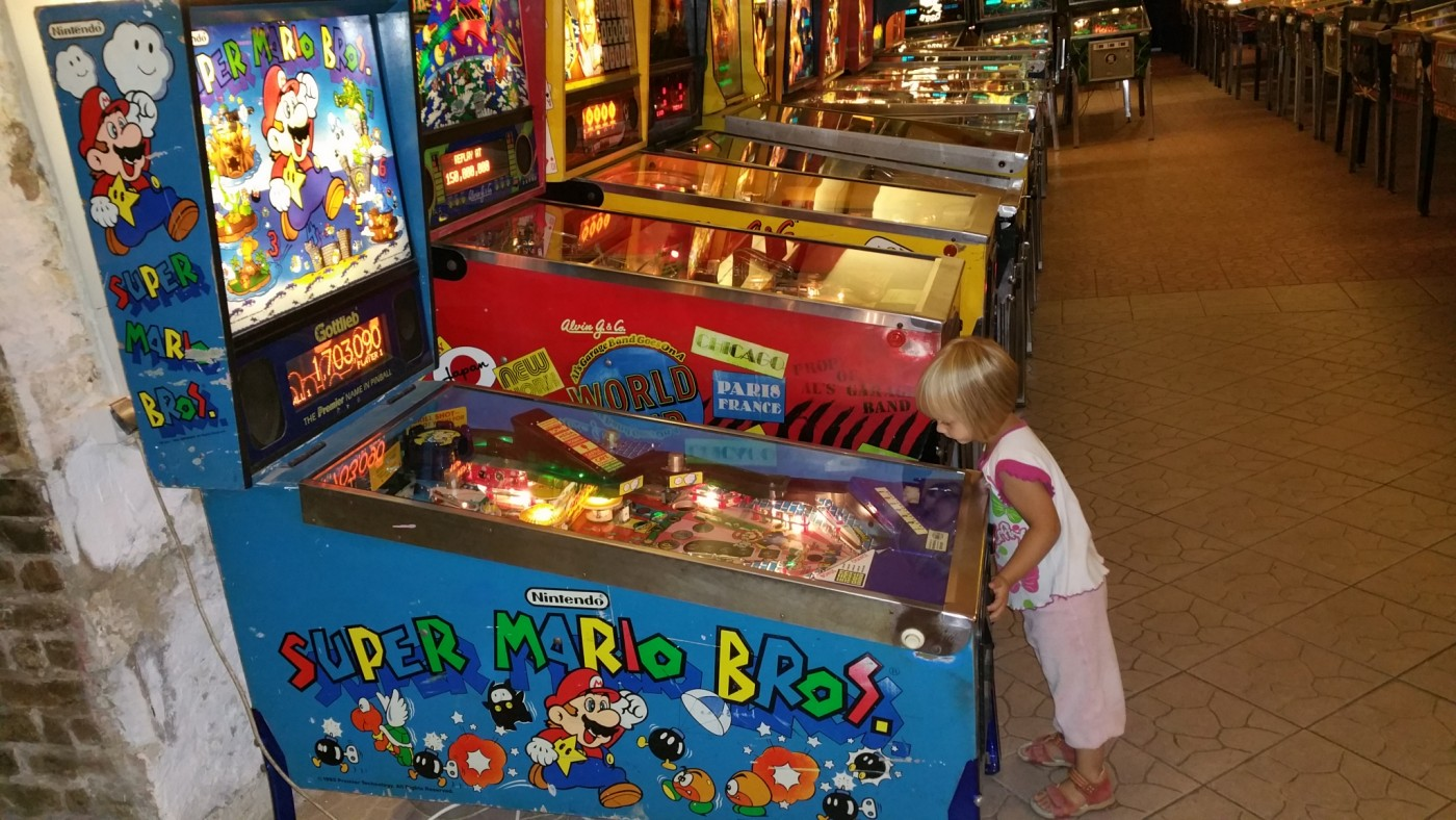 cute little girl playing pinball